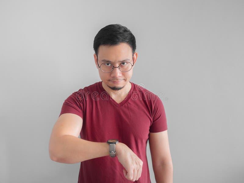 Verärgertes und unangenehmes Gesicht des Mannes betrachtet seine Uhraufwartung stockbild