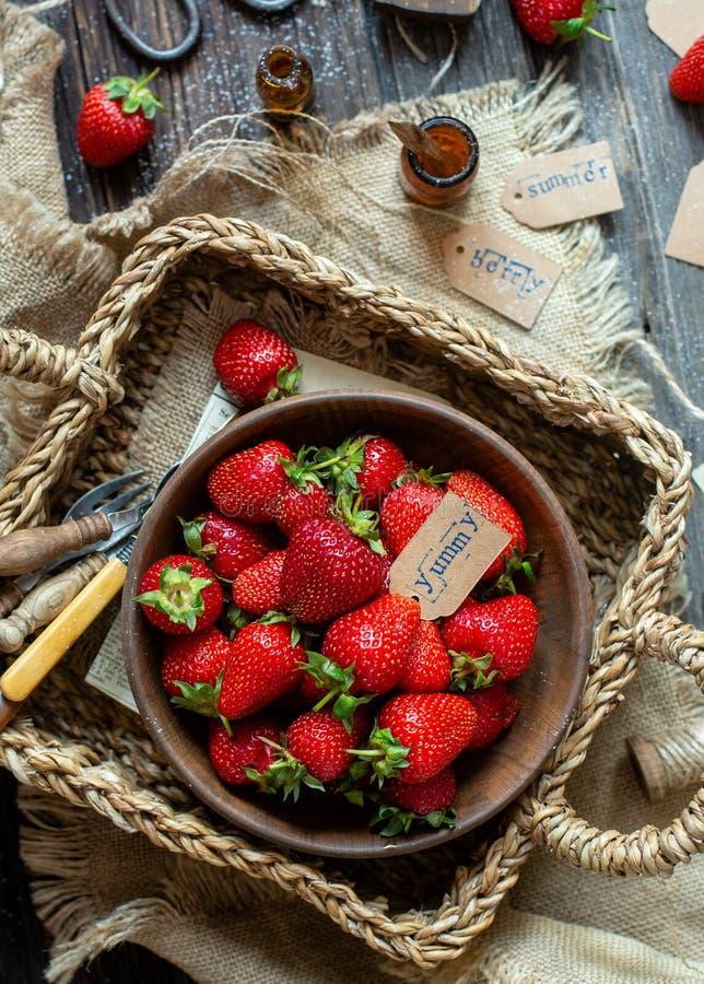 ?ver huvudet skott av smakliga mogna jordgubbar i tr?bunkest?llningar i vide- strawy korg p? den lantliga tabellen royaltyfri fotografi