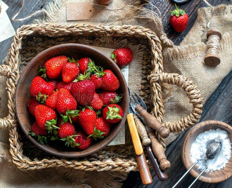 ?ver huvudet skott av smakliga mogna jordgubbar i tr?bunkest?llningar i vide- strawy korg p? den lantliga tabellen arkivfoton