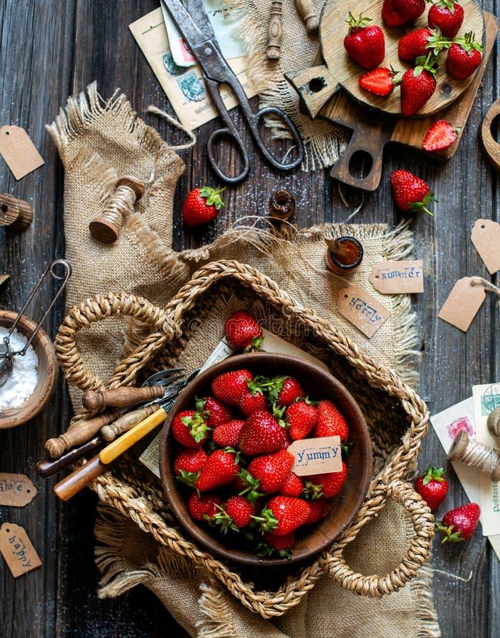 ?ver huvudet skott av smakliga mogna jordgubbar i tr?bunkest?llningar i vide- strawy korg p? den lantliga tabellen fotografering för bildbyråer