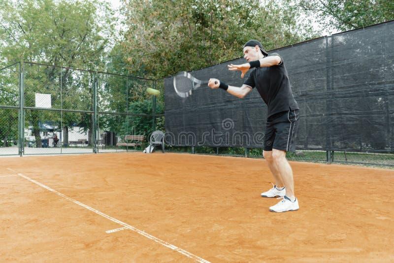 Ver plan van mensen speeltennis bij hof en het slaan van de bal met een racket stock afbeeldingen
