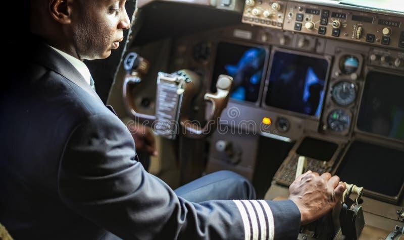 ?ver skuldran av en afrikansk pilot i en jumbocockpit arkivfoto