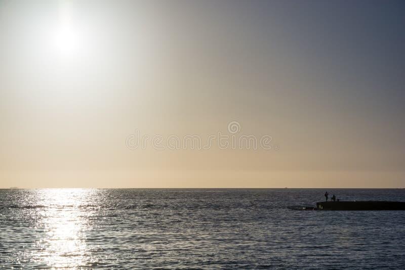 Ver van van een oceaan bij zonsondergang met vissers in de voorgrond stock foto's