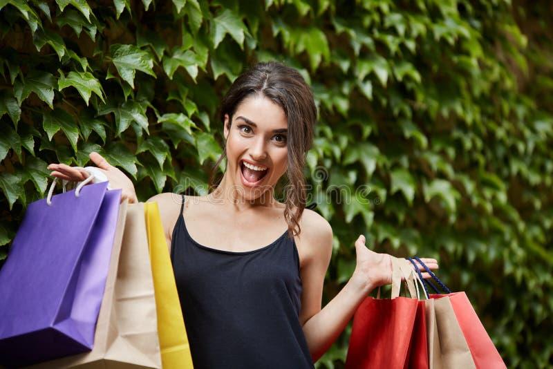 Vera felicità del ` s della ragazza Giovani belle donne caucasiche more in vestito nero che tiene grande quantità di borse variop fotografie stock
