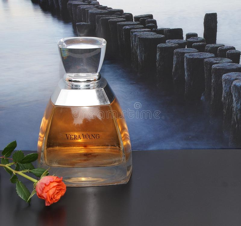 Vera Wang doft för damer, den stora doftflaskan av bilden av en vågbrytare i havet dekorerade framme med en ros royaltyfri bild