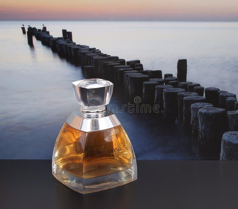 Vera Wang doft för damer, stor doftflaska framme av bilden av en vågbrytare i havet royaltyfri fotografi