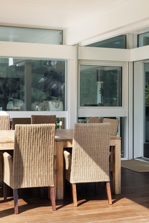 Veranda, vide- stolar och trätabell arkivfoton