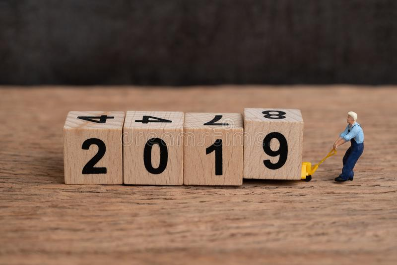 Veranderende concept van het jaar 2019 het nieuwe jaar, miniatuurmensenarbeider die het blok van de vorkheftruck bewegend kubus h stock fotografie