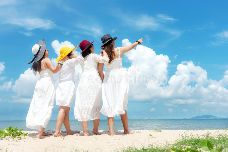 Verano blanco del vestido de la moda de la mujer asiática de la familia del grupo que lleva que coloca la playa arenosa del mar,  foto de archivo libre de regalías