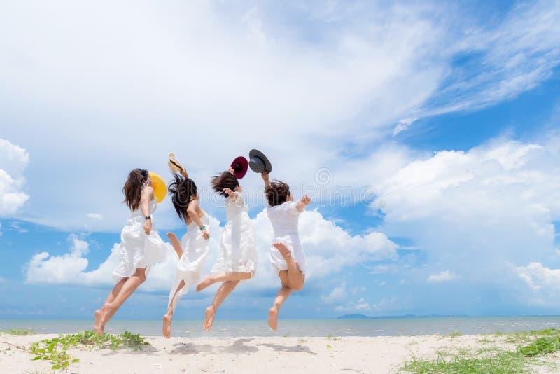 Verano blanco sonriente del vestido de la moda de la mujer asiática del grupo que lleva que camina la playa arenosa del mar, fond imágenes de archivo libres de regalías
