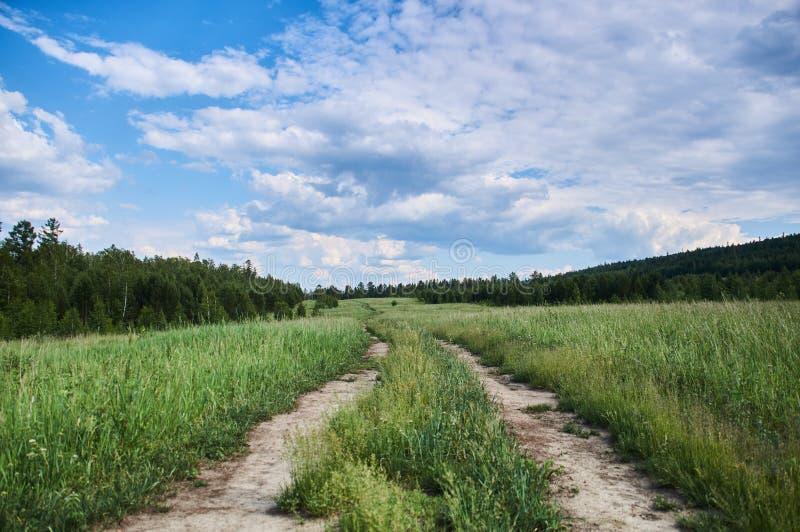 Verano Camino en campo debajo de las nubes gruesas fotos de archivo