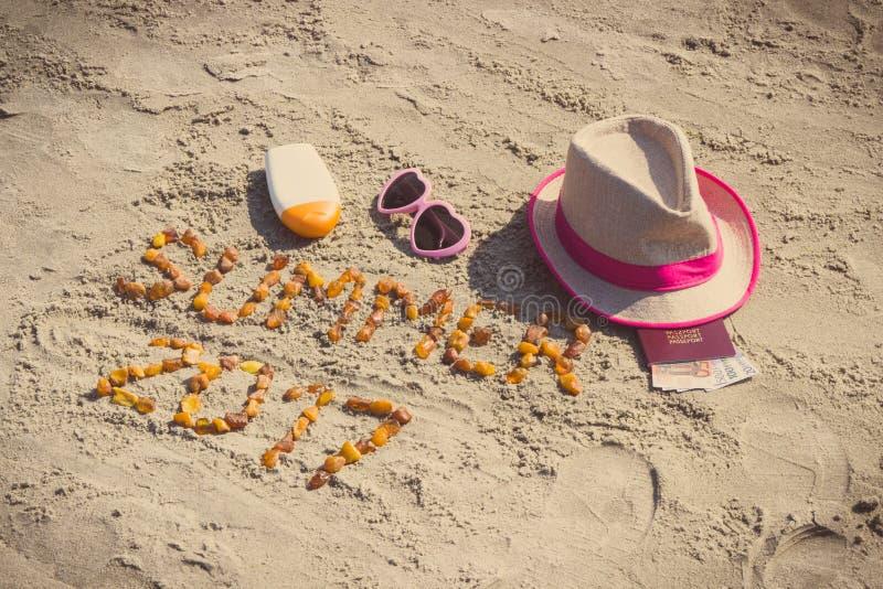 Verano 2017 de la inscripción, accesorios para tomar el sol y pasaporte con las monedas euro en la arena en la playa, tiempo de v fotos de archivo libres de regalías