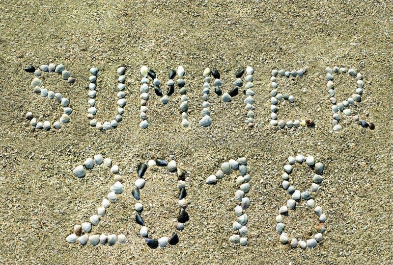Verano de 2018, las letras se dibujan en la playa arenosa foto de archivo