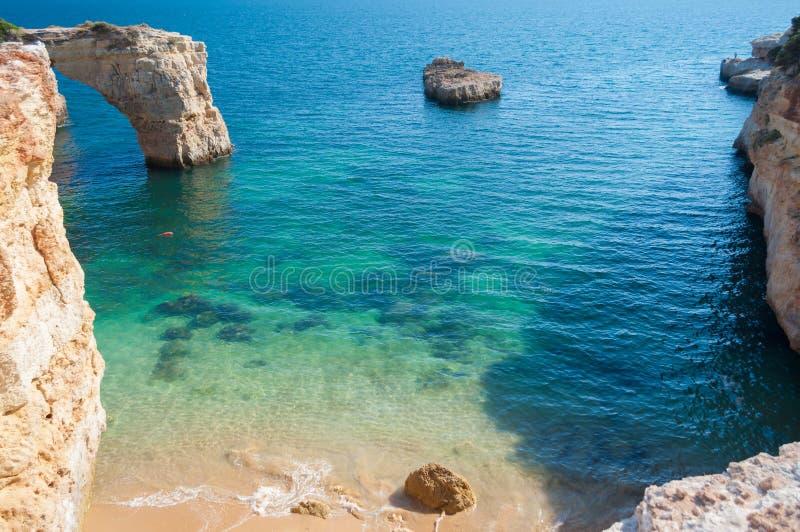 Verano en la costa de Algarve, Portugal Rocas en la línea de la playa y el agua azul imágenes de archivo libres de regalías