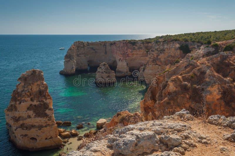 Verano en la costa de Algarve, Portugal Rocas en la línea de la playa y el agua azul imagen de archivo