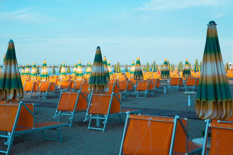 Verano italiano en el mar adriático: clubs italianos tyipical de la playa de Riviera Romagnola con los sunbeds y parasoles de pla fotos de archivo libres de regalías