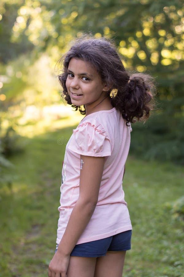 Verano la muchacha sonriente en pantalones cortos está en el jardín fotografía de archivo libre de regalías