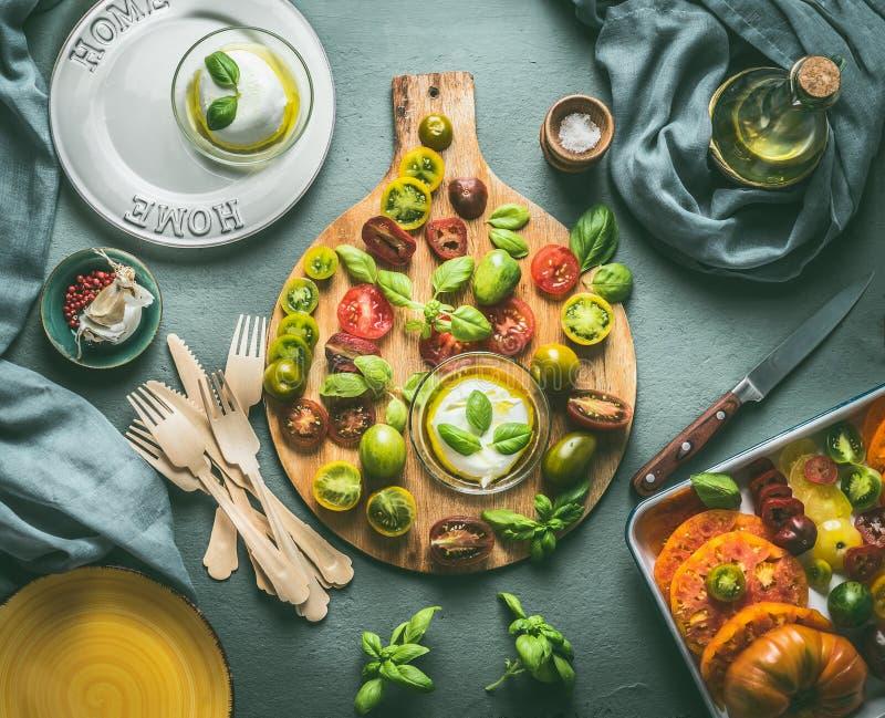 Verano o todavía de la comida vida italiana con la tabla de cocina, los tomates cortados frescos coloridos, la mozzarella, las pl imagenes de archivo
