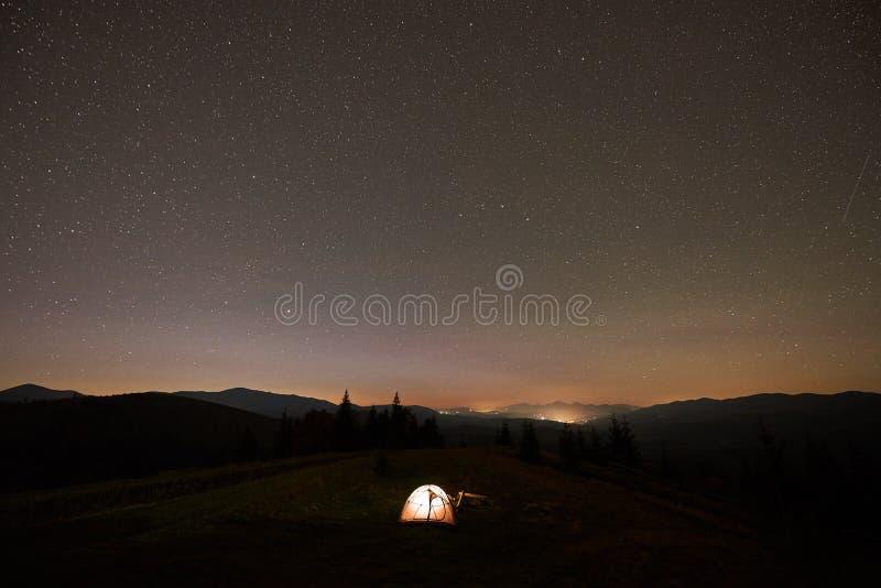 Verano que acampa en la noche Tienda tur?stica y hoguera ardiente en el valle verde debajo del cielo estrellado oscuro imagen de archivo
