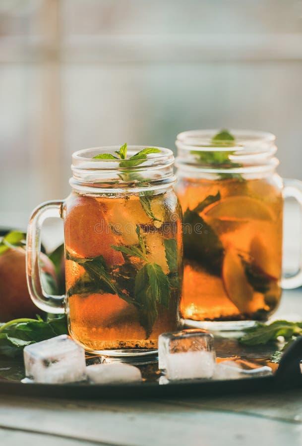 Verano que restaura té de hielo frío del melocotón en la bandeja, composición vertical foto de archivo