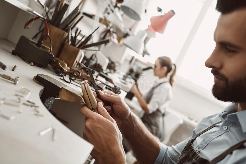 Verantwoordelijk voor zijn werk Zijaanzicht die van jonge mannelijke juwelier een ring maken bij zijn werkbank stock fotografie