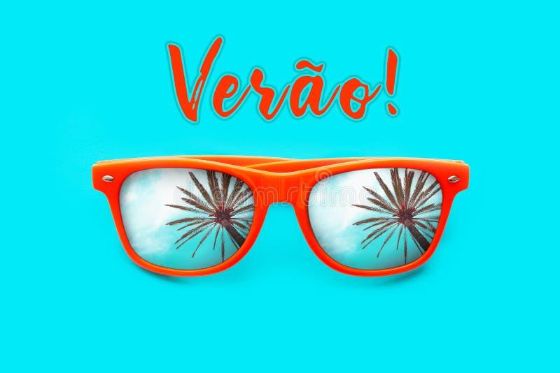 Veraotekst in het Portugees: De zomer en oranje die zonnebril met palmbezinningen op cyaanachtergrond worden geïsoleerd stock foto