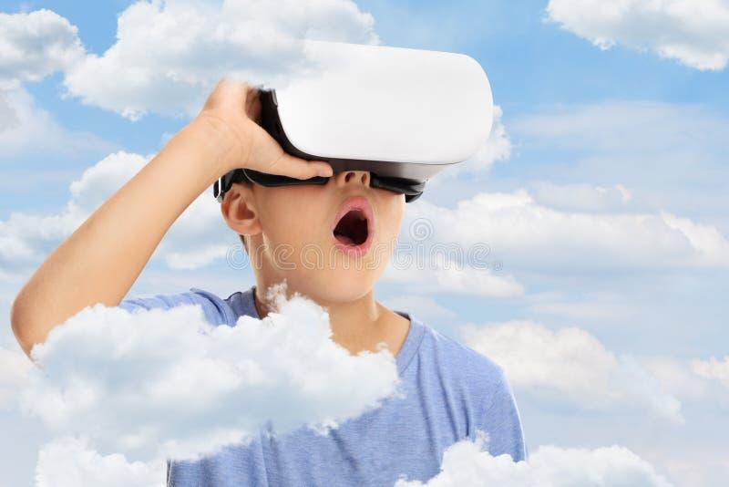 Verbaasd jong geitje dat in VR-beschermende brillen kijkt stock foto's