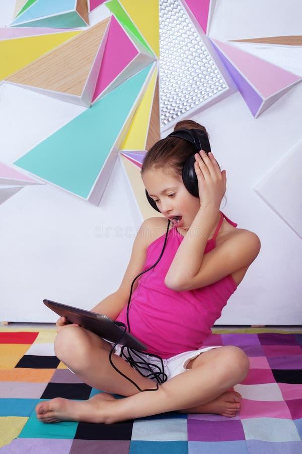 Verbaasd kindmeisje met een tablet in de ruimte Het concept van stock afbeeldingen