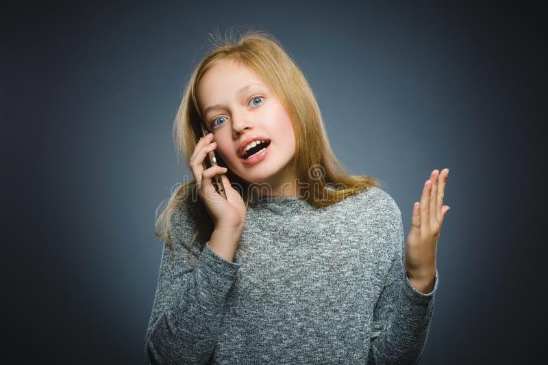 Verbaasd leuk meisje met celtelefoon Geïsoleerd op grijs stock fotografie