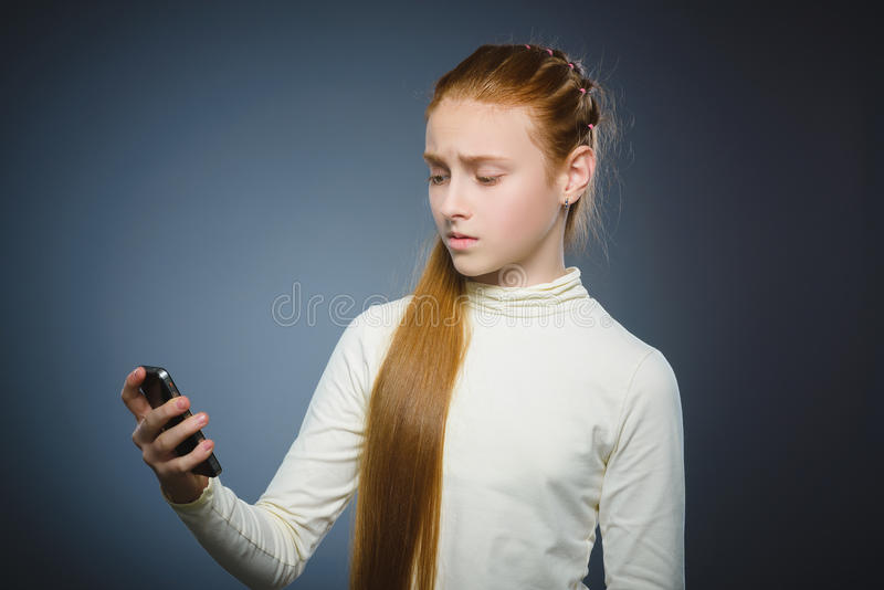 Verbaasd leuk roodharigemeisje met celtelefoon Geïsoleerd op grijs stock fotografie