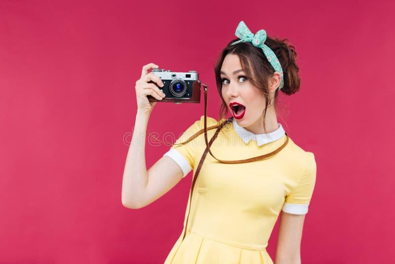 Verbaasd mooi pinupmeisje die in gele kleding oude camera houden stock foto