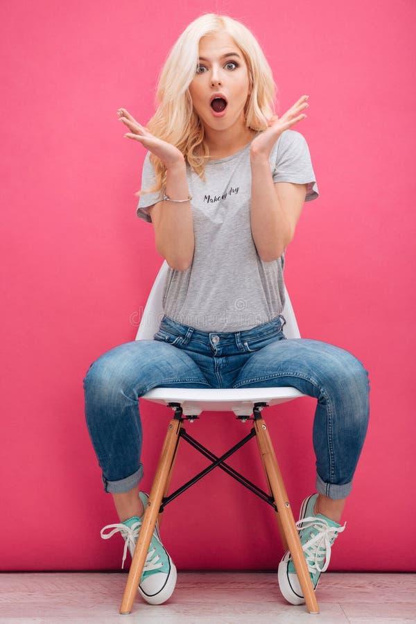 Verbaasde charmante vrouwenzitting op de stoel stock afbeelding