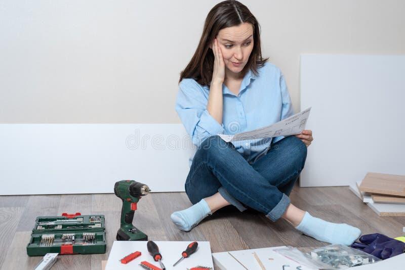 Verbaasde donkerbruine vrouw met de instructies voor Assemblage van meubilair in de handen van het zitten op de vloer met instrum royalty-vrije stock fotografie