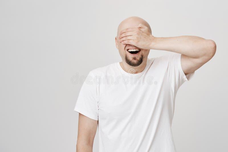Verbaasde en opgewekte kale gebaarde mens met brede glimlach die ogen behandelen met hand en voor iets wachten op positief aan royalty-vrije stock foto's