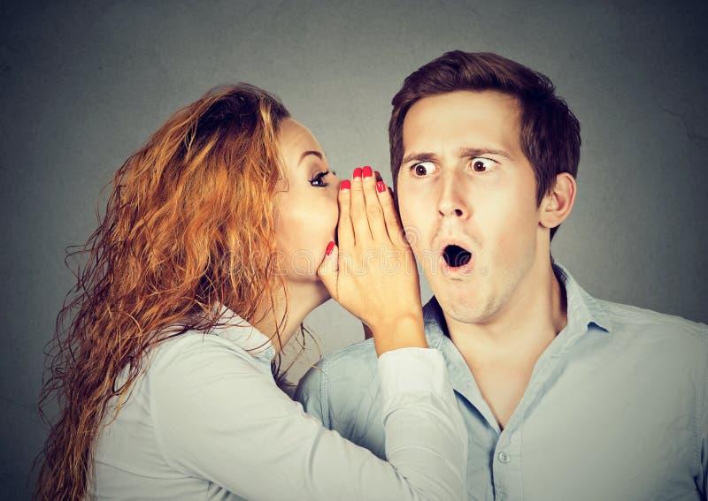 Verbaasde geschokte mens het luisteren roddel in het oor royalty-vrije stock afbeelding