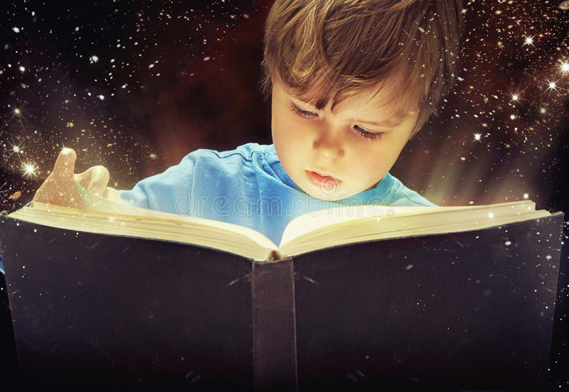 Verbaasde jonge jongen met magisch boek stock fotografie