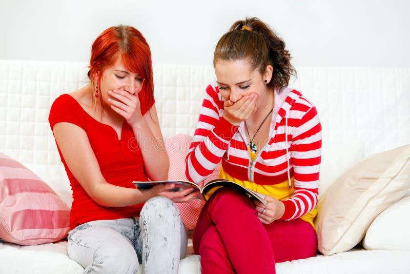 Verbaasde jonge meisjes die manier op tijdschrift letten stock afbeelding