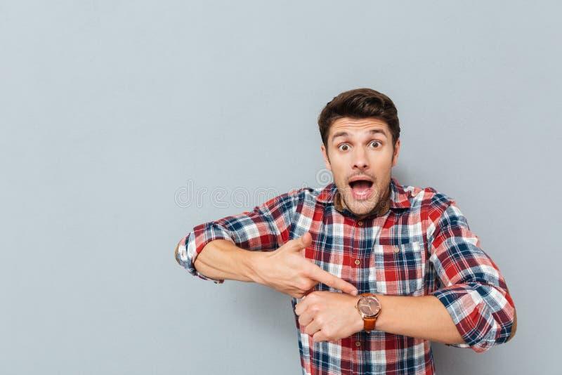 Verbaasde jonge mens die in plaidoverhemd op polshorloge richten royalty-vrije stock afbeelding