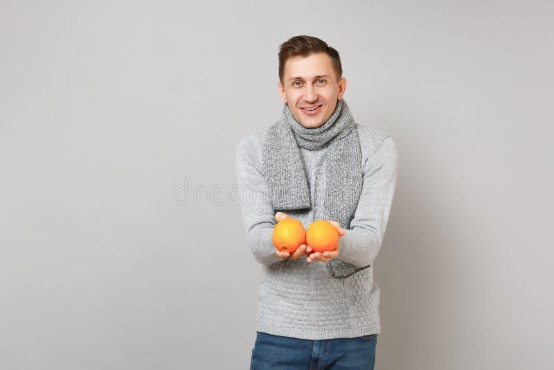 Verbaasde jonge mens in grijze sweater, de sinaasappelen van de sjaalholding op grijze muurachtergrond, studioportret Gezond royalty-vrije stock foto