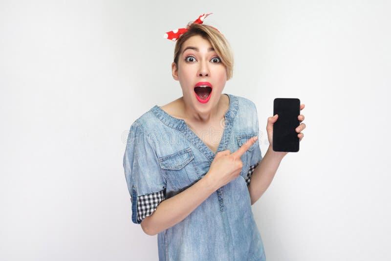 Verbaasde jonge vrouw in toevallig blauw denimoverhemd, rode hoofdband status, holding en het richten van vinger aan celtelefoon  royalty-vrije stock foto's