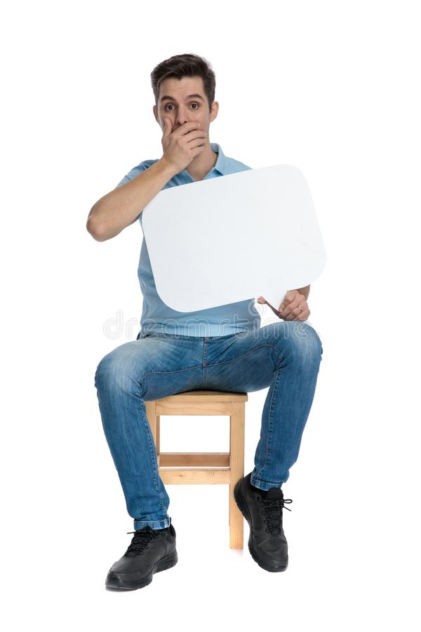 Verbaasde kerel die zijn mond behandelen en een toespraakbel houden stock foto