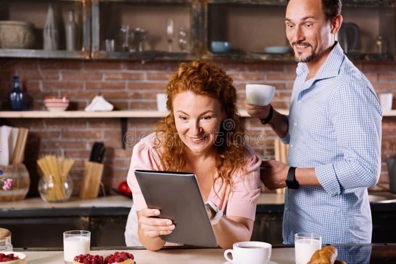 Verbaasde man en vrouw die tablet bekijken stock afbeeldingen
