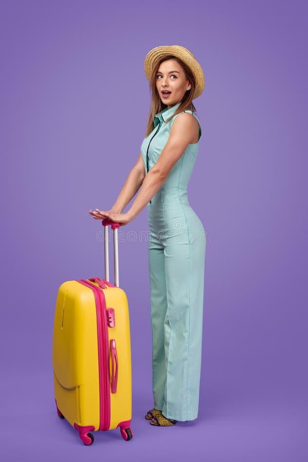 Verbaasde reiziger die met bagage weg kijken stock foto