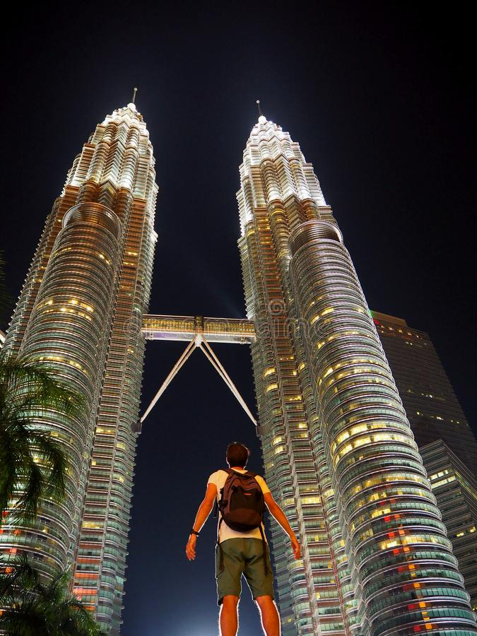 Verbaasde reiziger die omhoog aan de verlichte tweelingtorens van Petronas in Kuala Lumpur kijkt royalty-vrije stock foto