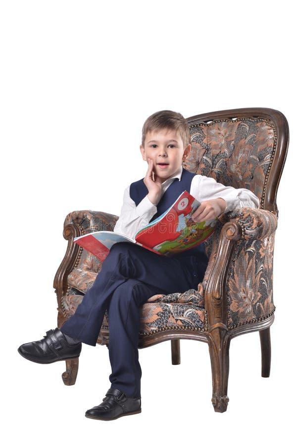 Verbaasde schooljongen in een antiek-ontworpen stoelgreep een open boek stock fotografie