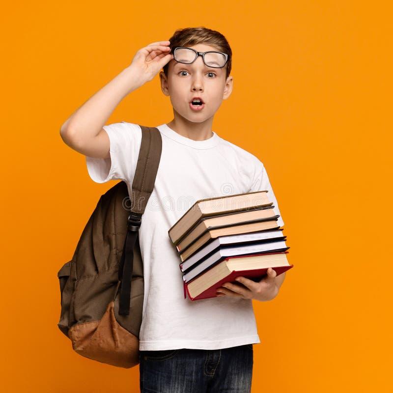 Verbaasde schooljongen in oogglazen met de hoop van de rugzakholding van boeken stock afbeelding