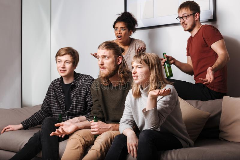 Verbaasde vrienden die op bank en het letten op film samen met bier thuis zitten royalty-vrije stock afbeelding
