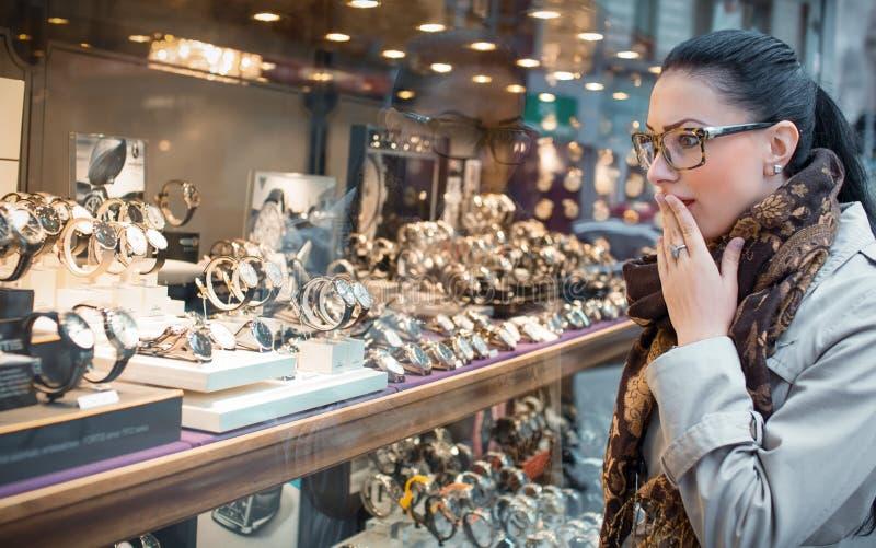 Verbaasde vrouw die aan showcase kijken royalty-vrije stock afbeeldingen