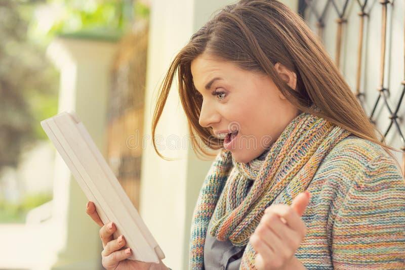 Verbaasde vrouw het letten op tablet op straat stock foto