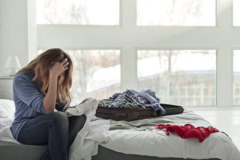 Verbaasde vrouwenzitting op bed stock foto